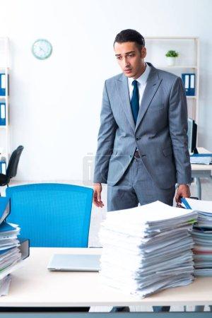 Photo pour L'homme d'affaires chargé d'une lourde paperasserie - image libre de droit