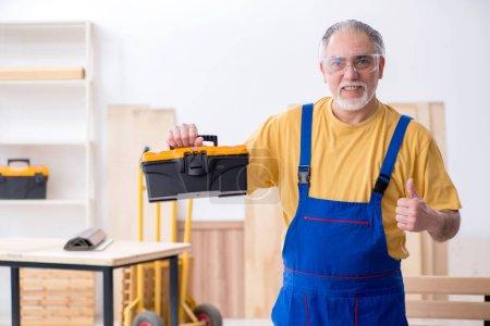 Photo pour L'ancien menuisier masculin travaillant en atelier - image libre de droit