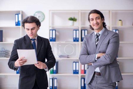 Photo pour Les deux jeunes hommes d'affaires réunis dans le bureau - image libre de droit