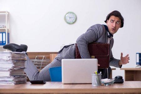 Photo pour Le jeune employé masculin mécontent d'un travail excessif - image libre de droit