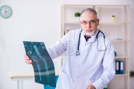 Photo for The old male doctor working in the clinic - Royalty Free Image