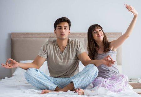 Photo pour La jeune famille méditant dans la chambre à coucher - image libre de droit