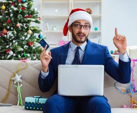 Photo pour L'homme d'affaires travaillant à la maison pendant Noel - image libre de droit