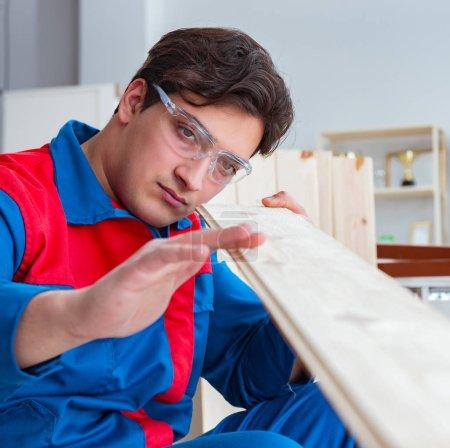 Photo pour Le jeune menuisier travaillant avec des planches en bois - image libre de droit