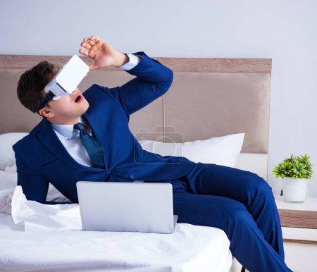 Photo pour L'homme d'affaires porte un casque d'écoute virtuel dans la chambre - image libre de droit