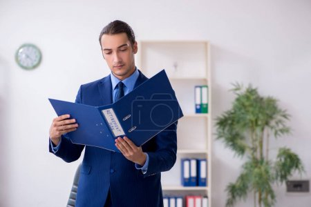 Photo pour The young male accountant working in the office - image libre de droit