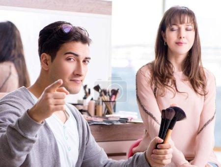 Photo pour Homme faire maquillage pour femme mignonne dans un salon de beauté - image libre de droit