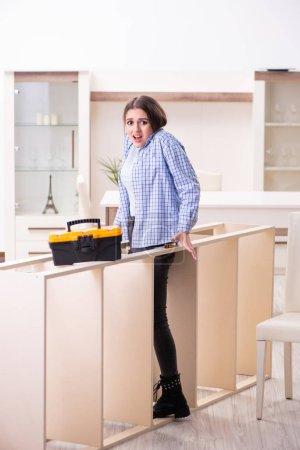 Photo pour The young beautiful woman assembling furniture at home - image libre de droit