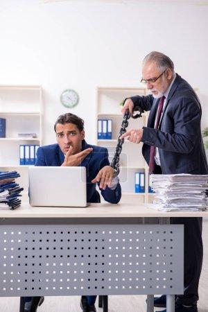 Photo pour Le vieux patron et jeune employé masculin dans le bureau - image libre de droit