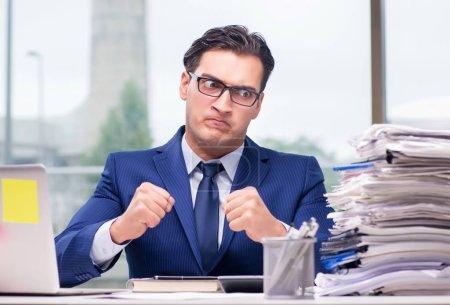 Photo pour Le bourreau de travail surmenait avec trop de travail au bureau - image libre de droit