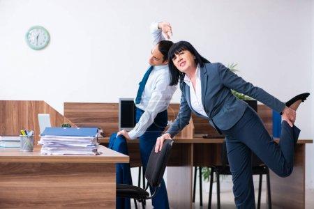 Photo pour Les deux employés faisant des exercices sportifs dans le bureau - image libre de droit
