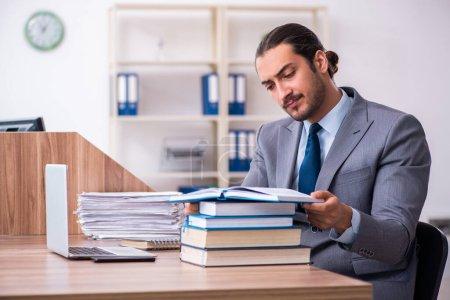 Photo pour Jeune entrepreneur lisant des livres sur son lieu de travail - image libre de droit