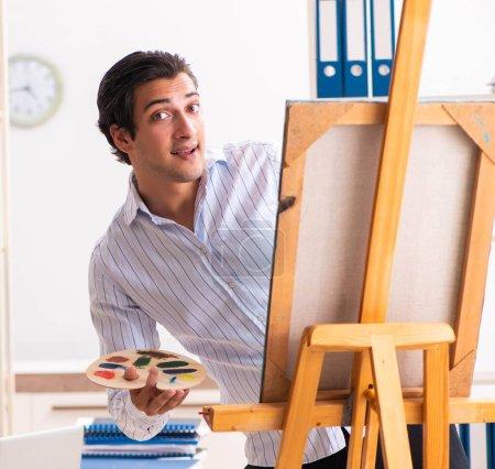 Photo pour Le jeune et beau employé qui aime peindre au bureau - image libre de droit