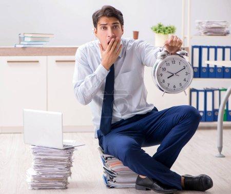 Photo pour L'employé extrêmement occupé qui travaille au bureau - image libre de droit