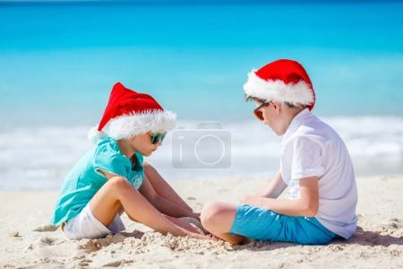 Photo for Kids in red Santa hats having fun at tropical beach during Christmas vacation playing together with sand - Royalty Free Image