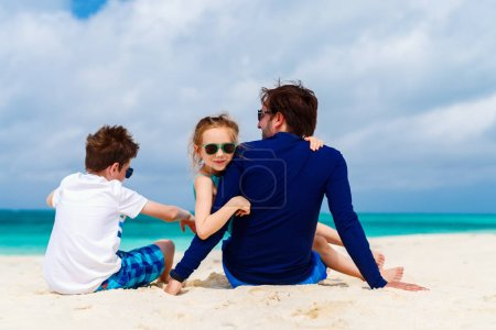Father with kids at beach