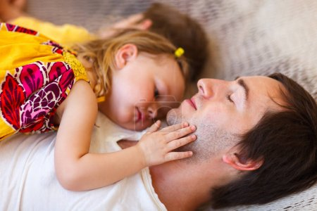 Father and daughter relaxing in hammock