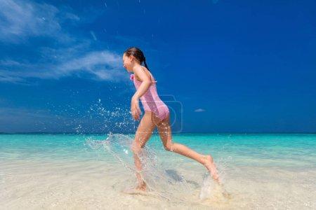Photo pour Bonne petite fille courir et éclabousser à l'eau peu profonde à la plage avoir beaucoup de plaisir pendant les vacances d'été - image libre de droit