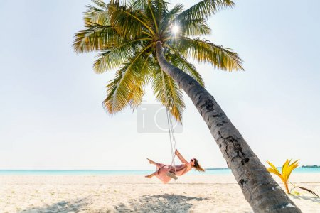Young beautiful woman relaxing in a swing hanging on coconut palm at tropical beach