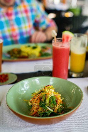 Photo for Delicious vegetable salad served for lunch with drinks on background - Royalty Free Image