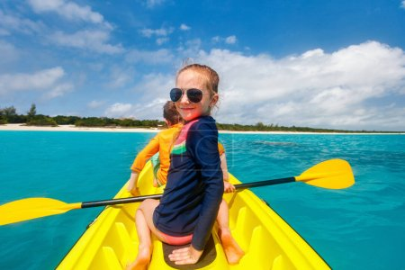 Family with kids paddling on colorful kayaks at tropical ocean water during summer vacation
