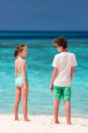Kids brother and sister at tropical beach during summer vacation