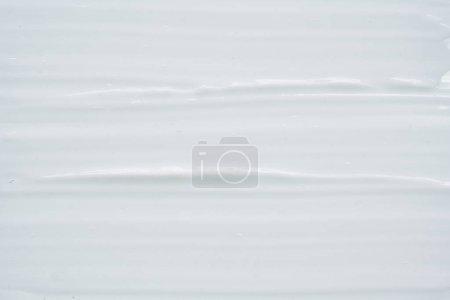 weiße Textur und Abstrich von Gesichtscreme oder weißer Acrylfarbe isoliert auf weißem Hintergrund