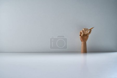 Photo for Wooden hand with pencil on a gray background - Royalty Free Image