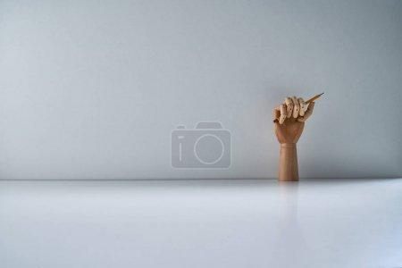 Photo pour Main en bois avec crayon sur fond gris - image libre de droit