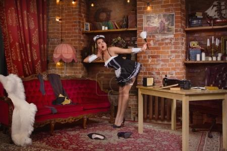 Photo for Young sexy chambermaid with duster. Pin up housework. - Royalty Free Image
