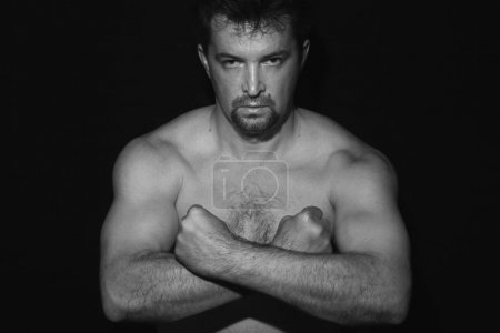 Photo for Muscular man showing his muscles. Black and whit - Royalty Free Image