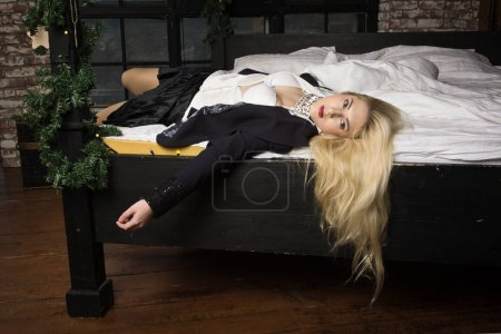 Strangled business woman lying on the bed