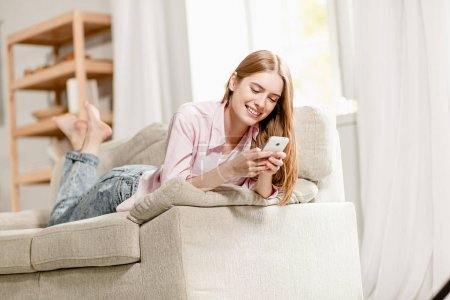 Young charming girl, relaxing on sofa, sending sms to a friend.