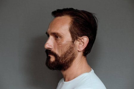 Side view of mans face on grey background.