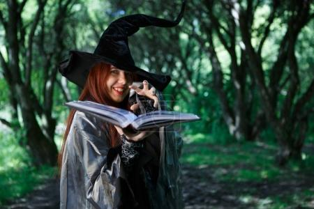 Image of young laughing witch with book