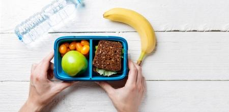 Photo of mans hands with useful lunch in box