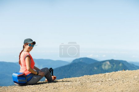 Photo of smiling girl sitting on edge of hill