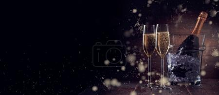 Holiday photo of wine glasses on wooden table with bucket