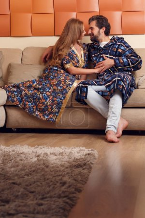 Photo of woman and man in home clothes hugging on sofa