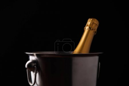Image of bottle of champagne in iron bucket