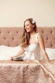 Image of happy woman in white negligee sitting on bed