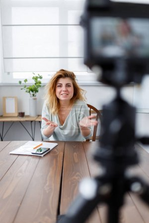 Blurred photo of woman blogger sitting at table.