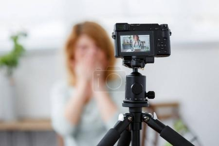 Defocused image of florist woman covering face with hands at table with florarium.
