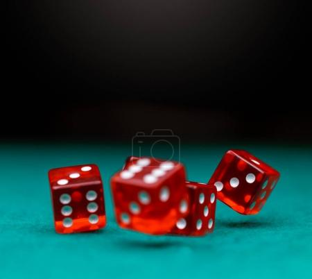 Image of several red dice falling on green table