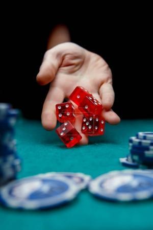 Photo pour Image de l'homme en jetant les dés rouges sur table avec jetons au casino, fond noir - image libre de droit