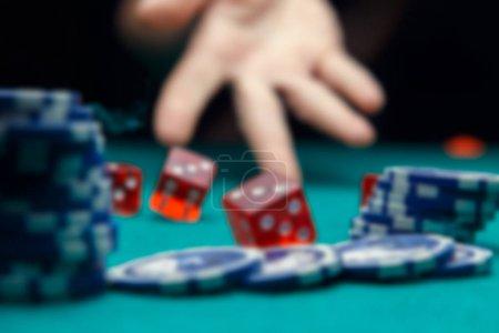 Defocused photo of dice, chips, palm in casino