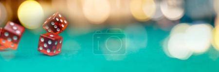 Photo pour Image de plusieurs dés rouges tombant sur une table verte sur fond de spots multicolores, un espace vide pour texte - image libre de droit