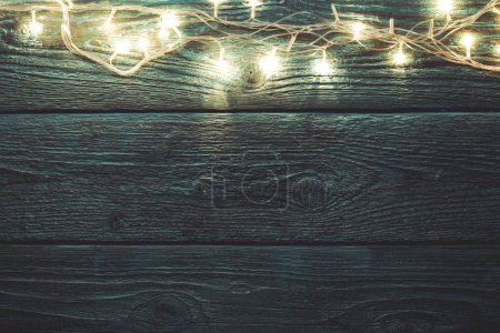 Image of green wooden table with burning New Years garland.