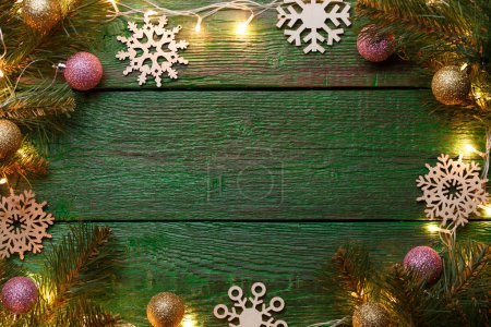 Photo of New Years background with burning garland around perimeter, branches of spruce, Christmas balls, snowflakes