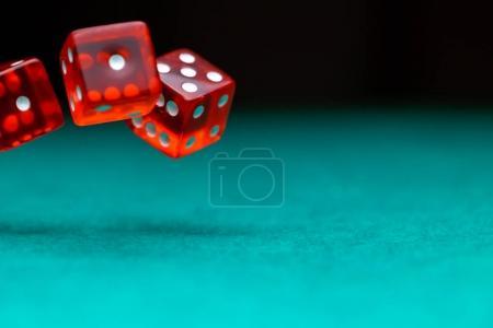 Photo pour Photo de plusieurs dés rouges tombant sur une table verte sur fond noir dans le casino, un espace vide pour texte - image libre de droit